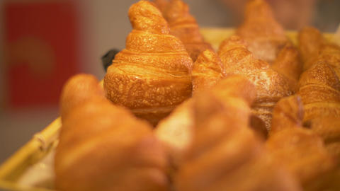 Freshly baked croissants from puff pastry in straw basket in bakery close up Footage