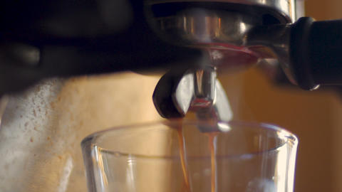 Side view of fresh steaming hot coffee pouring from a stainless steel expresso Footage