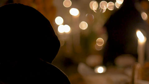 Person covered with a hoodie or scarf sitting by candle light at night in a Live Action