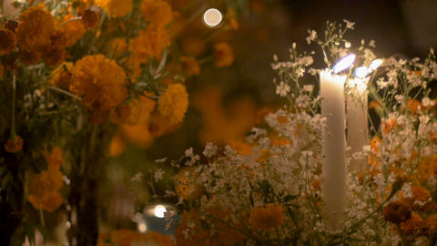 White candles burning at night next to marigold flowers during day of the dead GIF
