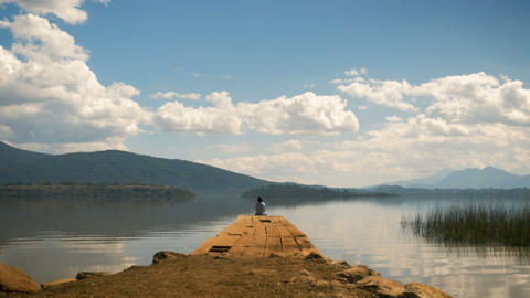 Man sitting at the edge of a dock on a beautiful peaceful mountain lake Footage