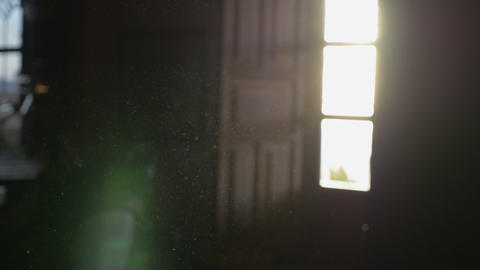 Dust floating in the air of a dark room with an open window and sunglare Footage