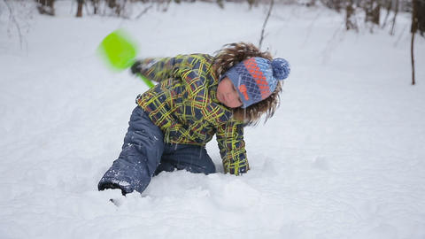 Cute little funny boy , having fun on snow in winter, outdoors during snowfall.  Footage