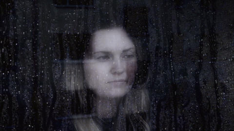 Sad and thoughtful young woman looking through a window Footage