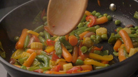 Frying vegetables on black pan Footage