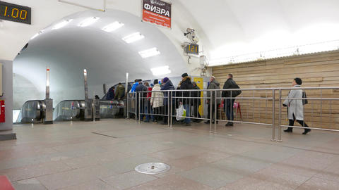 Short commuters queue to metro escalators at connected stations Footage