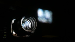 Blurred image on glass, sharp lens, bright beam from cinema projector, dark room Footage