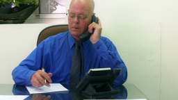 Businessman on phone taking notes dolly in HD Footage