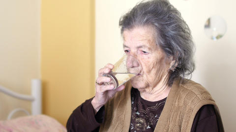 Unhealthy Old Woman Get Pills, Drink Water stock footage