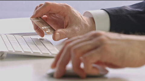 Male hands holding credit card and using mouse Footage