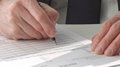 male hand in suit filling in invoice paper Live Action