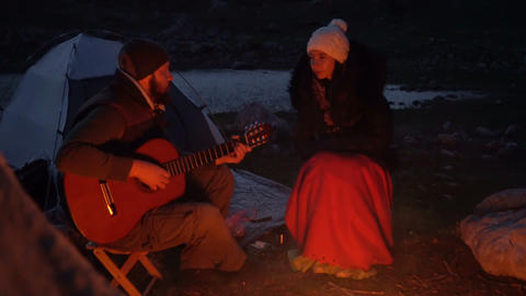 Couple of travelers at dusk near a campfire Footage
