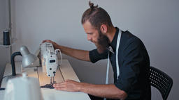 Handsome Bearded Tailor is Working on Sewing Machine in his Fashion StartUp Footage