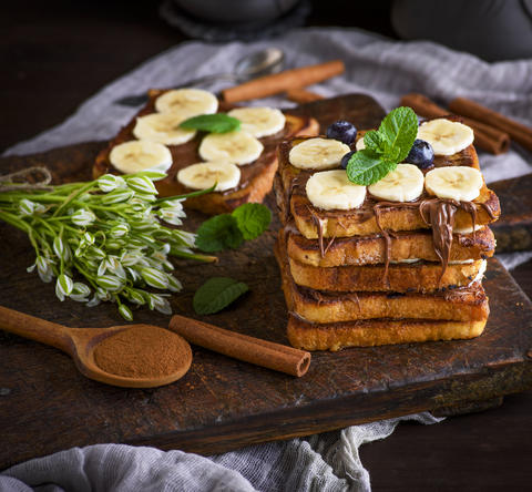 French toast with chocolate and banana slices on a brown wooden フォト