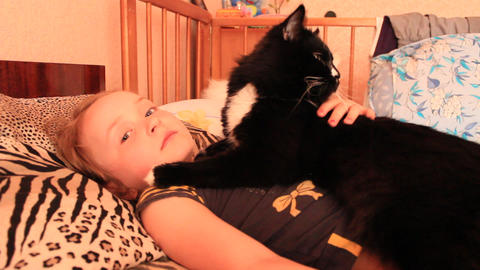 Little girl laying in bed together with her cat. Together with your pet Live Action