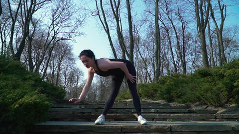 Young brunette makes sport exercises in park Footage
