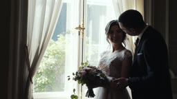 Marrying couple embrace and kiss standing near huge window in room GIF