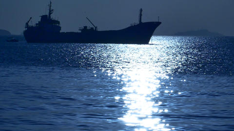 Cargo ship silhouette in the moonlight reflected on the water. Freighter Footage