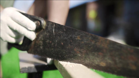 Man saws up the wooden bar by the rusty handsaw outdoors, DIY works with wood Footage