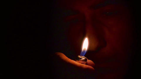 Closeup Man lights up a lighter in the darkness. Slow Motion Macro Video. Footage