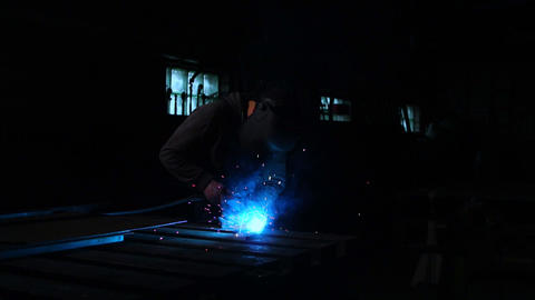 The welder works in a mask in slow motion. Sparks fly in different directions 영상물