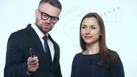 Man and woman shake hands and discuss the business strategy for success in a Footage
