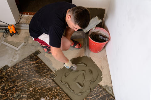 Master husband presses a spatula glutinous solution to the cement surface Fotografía