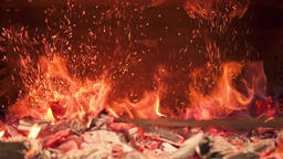 Burning coals in the stove are mixed creating a fiery dust. Slow motion Footage