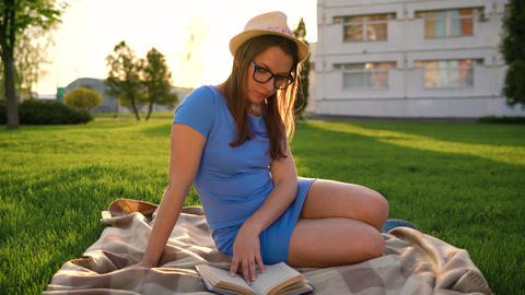 Girl in glasses reading book sitting on a blanket in the park at sunset Footage