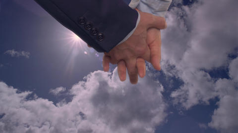 Female hand holding male hand in lock on sky background. Close up man hand Live Action