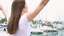 Young woman standing alone on pier. Inspired carefree female raising her arms up Footage
