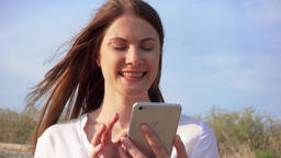 Woman use mobile against blue sky. Smiling female chatting with friends via Footage