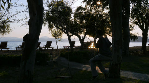 man on swing, swinging at sunset Footage