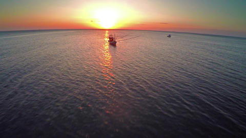 Flying over fishing boats in the sea at sunset Footage
