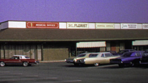 1974: Fifth avenue florist strip mall store classic car parking lot Footage