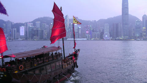 Junk boat sailing across Victoria Harbour and city skyline Live Action
