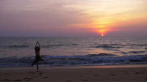 Young beautiful woman doing yoga on the beach at sunset - vrksasana (tree pose) Footage