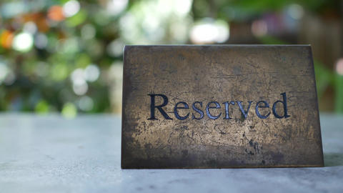 rough metal reserved sign on dining table in restaurant, beautiful bokeh as Live Action