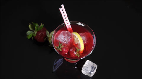 Red cocktail with fresh strawberries and ice cubes Footage