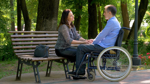Young man on wheelchair talking with his wife in park Archivo