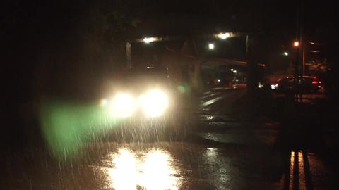 Off-road vehicle coming out on a side road in the rain that sees the headlights  Footage