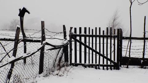 Wooden gate and fence that surrounds the property in the path that rummages snow Footage