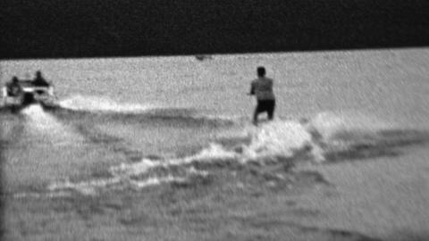 1962: Waterski man pulled behind speedboat dark mysterious lake Footage