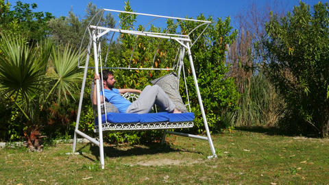 Swinging caucasian man sleeping on hammock at garden, swing Footage