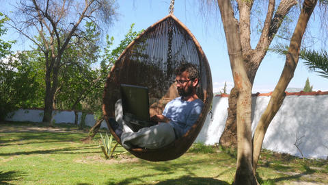 Freelance worker on hammock swing, working online, typing laptop keyboard Footage