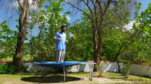 Happy man jumping playing on trampoline, freedom happiness concept Footage