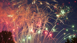 Many firecrackers explode in sky, small spots of light, rockets flash with sound Footage