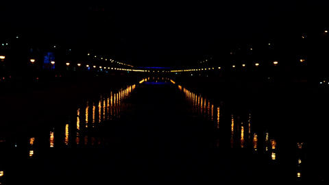 Lights from lighting poles which are reflected in the water that crosses the cit Footage