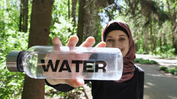 Portrait of a cute young girl in a hijab with a bottle of water in her hands 영상물