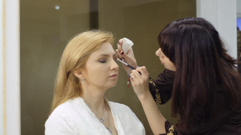 Beautician makes makeup for mature woman in beauty saloon 影片素材